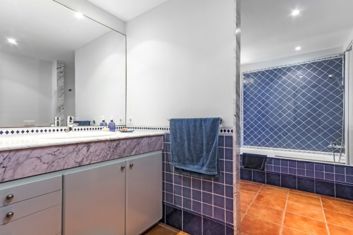 Blue bathroom with large mirror