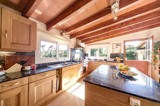 Large and fully equipped kitchen with wooden ceiling beams